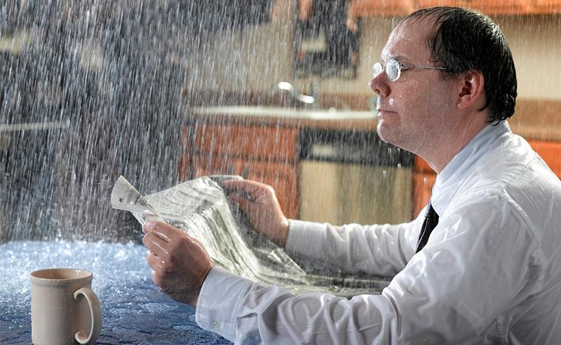 En mann som leser avis i regnet