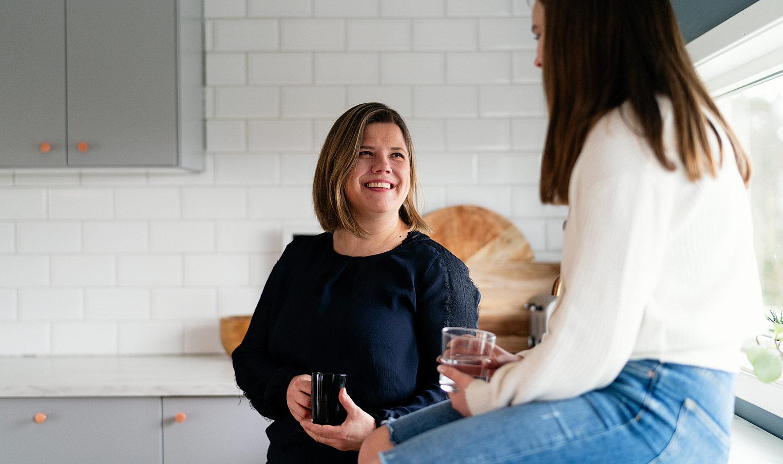 kvinne og yngre kvinne som sitter på et renovert kjøkken